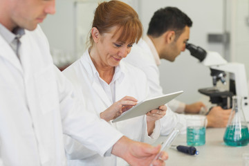 Amused mature scientist working with her tablet