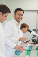 Handsome male scientist holding his white tablet standing in the laboratory