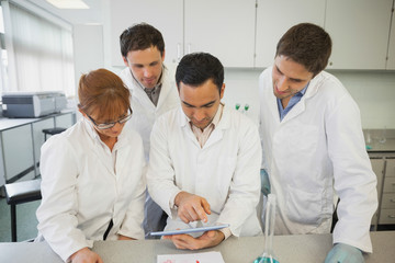 Young male scientist showing his tablet to his colleagues