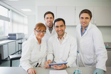 Some scientists standing behind a desk in the laboratory holding a tablet