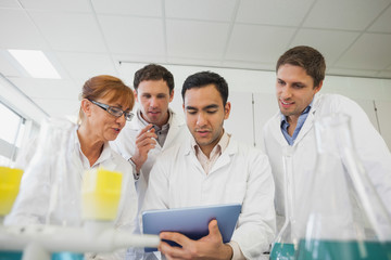 Low angle view of some scientists looking at a tablet