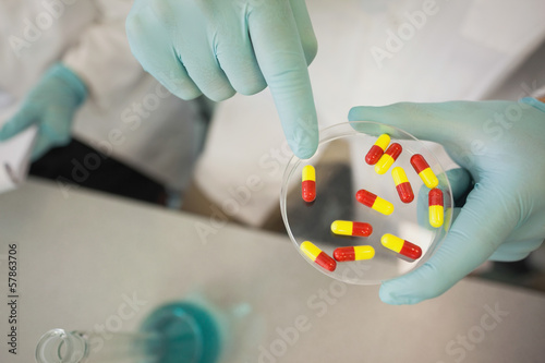 Extreme close up of scientist holding a petri dish filled with pills