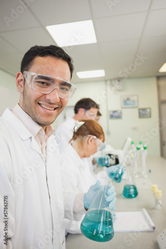 Young male scientist holding an erlenmeyer flask standing in a laboratory