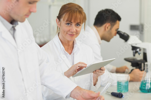 Female mature scientist using her tablet in the laboratory