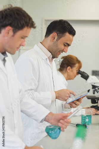 Amused young scientist working with his tablet