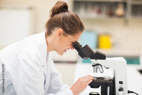 Smiling brunette student looking through microscope