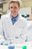 Cheerful handsome student in lab coat looking at camera