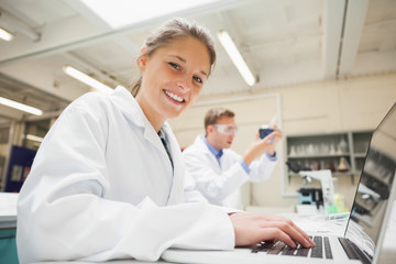 Cheerful student working at laptop and looking at camera