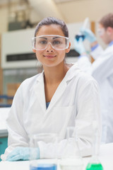 Happy attractive student in lab coat looking at camera