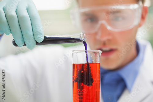 Amazed student pouring purple liquid into red