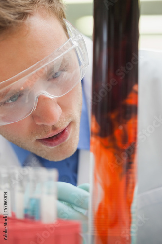 Amazed student watching purple liquid mixing with red