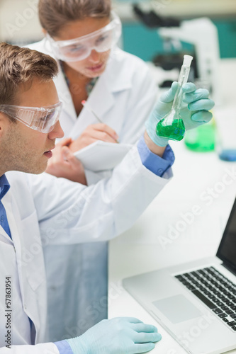 Two students examining green liquid and taking notes