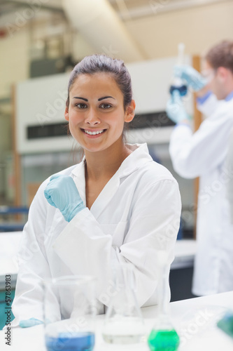 Smiling attractive student in lab coat looking at camera
