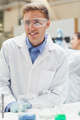 Smiling handsome student in lab coat looking at camera