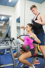 Instructor assisting toned brunette at weight machine