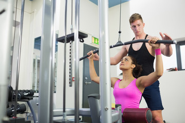 Instructor assisting fit brunette at weight machine