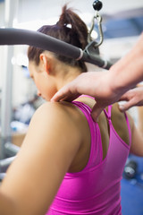 Instructor correcting shoulder position of woman working out