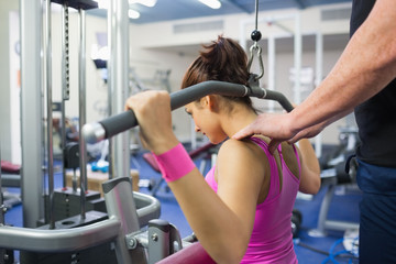 Instructor correcting shoulder position of woman of working out