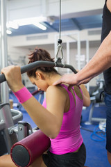 Trainer correcting shoulder position of woman of working out