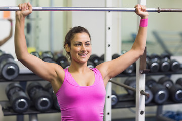 Sporty cheerful brunette holding barbell