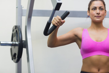 Calm sporty brunette training her arms