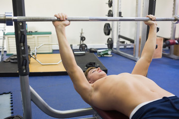 Handsome muscular man lying on bench lifting barbell