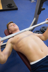 Good looking muscular man lying on bench lifting barbell