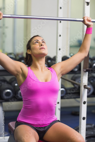 Sporty brunette holding barbell
