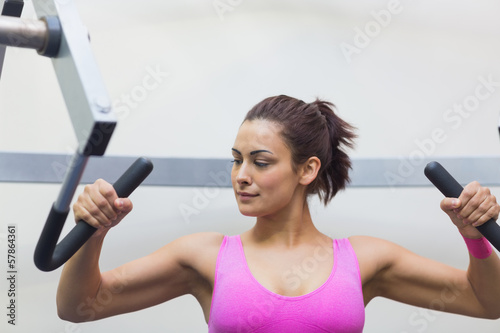 Focused toned brunette training her arms
