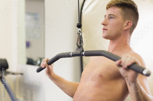 Attractive muscular man training on weight machine