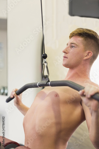 Handsome muscular man training on weight machine