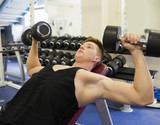 Muscular focused man lying on bench training with dumbbells