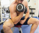 Muscular handsome man sitting on bench training with dumbbells