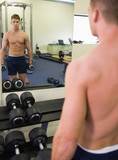 Reflection of muscular man holding dumbbells