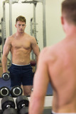 Reflection of muscular topless man holding dumbbells