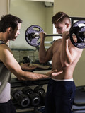 Instructor correcting topless man lifting barbell