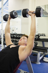 Muscular concentrating man lying on bench training with dumbbells