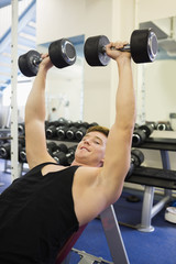 Muscular happy man lying on bench training with dumbbells