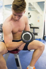 Muscular topless man sitting on bench training with dumbbells