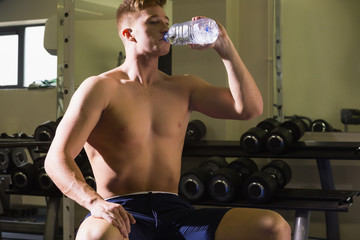 Muscular handsome man sitting on bench drinking from water bottle