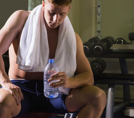 Frowning muscular man sitting on bench holding water bottle