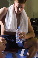 Serious muscular man sitting on bench holding water bottle