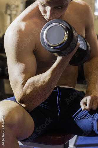 Muscular man sitting on bench posing with dumbbells