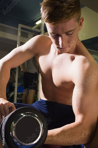 Muscular topless man lifting dumbbells