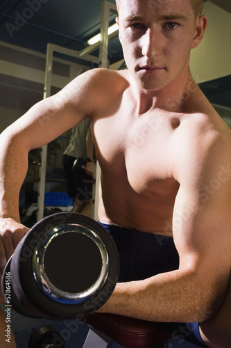 Muscular serious man lifting dumbbells