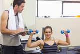 Instructor taking notes of smiling brunette lifting dumbbells