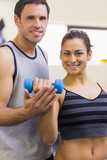 Instructor assisting smiling brunette lifting dumbbells
