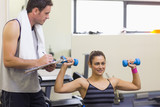Instructor taking notes of happy brunette lifting dumbbells