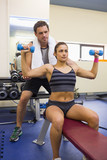 Trainer correcting toned brunette lifting dumbbells