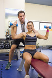 Trainer correcting smiling brunette lifting dumbbells